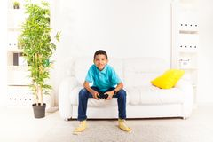Time to play videogame. Happy smiling black boy playing video games holding game controller sitting on the white sofa in living room Stock Photos
