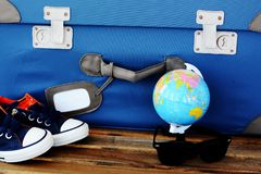 Time to prepare for holiday with retro suitcase, passport, sneakers and globe on wooden table – travel concept. Time to prepare for holiday with blue Royalty Free Stock Photography