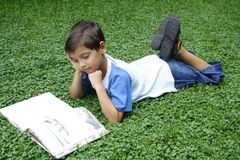 Time to read. Boy on the grass with a book Royalty Free Stock Images
