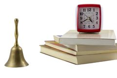 Time to read a book. Old clock and a bell with stack of books, isolated white background Stock Images