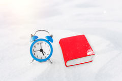 Time to read. Book and vintage alarm clock on the snow. The concept of Christmas and New Year. Stock Photo