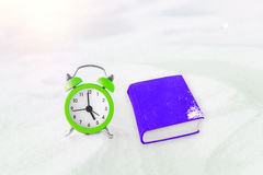 Time to read. Book and vintage alarm clock on the snow. The concept of Christmas and New Year. Stock Photography