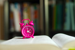 Time to read. A little magenta alarm clock standing on an open book. A blurred bookshelf is in the background stock images