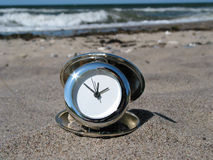 Time to relax!. Chrome clock lying on the beach with the ocean in the background Stock Photo