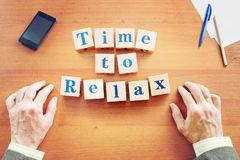 Time to relax. Businessman made text from wooden cubes stock images