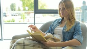 Concentrated young woman reading book stock video footage