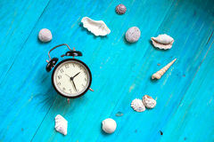 Time to relax, watch, seashells, blue wood background, concept h Stock Image