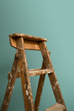 Time to renovate. An old rustic ladder standing against a green wall Stock Photos