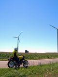 Time to Ride. A motorcycle rider took a break to checkout the massive windmills Stock Images