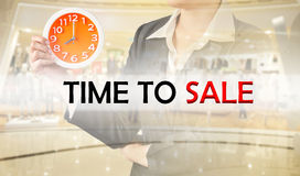 Time to sale, Business concept. Time to sale, and business woman holding clock on blurred shopping mall. Business concept Stock Image