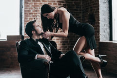 Time to seduce. Beautiful young women in cocktail dress leaning to her boyfriend sitting in chair while looking at each other in loft interior Stock Photos