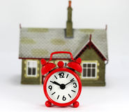 Is it Time to Sell or Buy!. A red Alarm clock in front of a house, asking the question is it time to sell or buy stock images