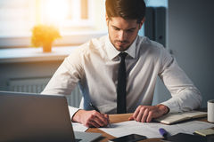 Time to sign some contracts. Pensive young handsome man signing documents while sitting at his working place Stock Image