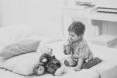 Time to sleep concept. Child in bedroom with silence gesture. Boy with happy face puts favourite toy on bed, time to. Sleep. Kid put plush bear near pillows and stock images