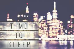 Time to sleep text in a lightbox, blurred Manhattan at night. Royalty Free Stock Images