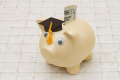 Time to start saving for college, A piggy bank and graduation ca Royalty Free Stock Photography