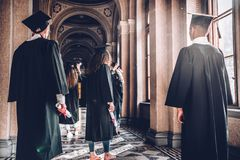 Time to step into a new world.Rear view shot of a group of students standing in the university hall.  royalty free stock images