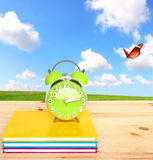 Time to study, time for nature. Green alarm clock of a retro style on the desktop with nature landscape in the background Royalty Free Stock Photo