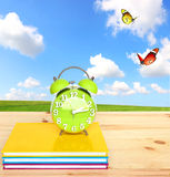 Time to study, time to travel. Green alarm clock of a retro style on the desktop with nature landscape in the background Royalty Free Stock Images