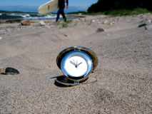 Time to surf!. Chrome clock lying on the beach with a surfer in the background Royalty Free Stock Photos
