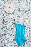 Time to swim. time to do aquagym. Wall clock on the tile in the pool. on the hook a one-piece sports swimsuit and a swimming cap. Time to swim, preparation for Stock Image