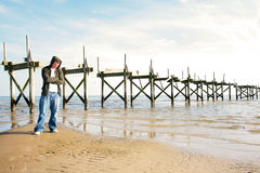 Time to Think. A man standing alone wearing a hooded sweatshirt with an old pier in the background Stock Photo