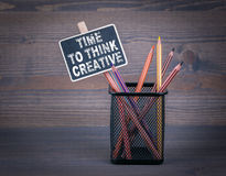 Time to think creative. A small blackboard chalk and colored pencil on wood background Royalty Free Stock Photos