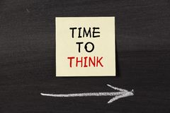 Time To Think. Sticky note pasted on a blackboard background with a chalk arrow royalty free stock image