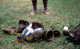 A time to throw stones. Legs in a bast shoes, helmet and armour on the groung after the tournament Royalty Free Stock Image