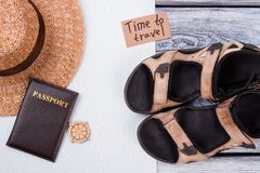 Time to travel and beach rest concept flat lay. Summer footwear, straw hat and passport on white and wooden background Stock Images