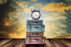 Time to travel concept. Alarm clock on travel bag with sunset sky background Stock Image