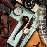 Time to travel concept, hipster flat lay. map passport compass a. Nd glasses pipe camera  feathers on black  wooden background top view. planning vacation. space Royalty Free Stock Photography