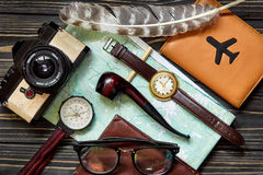 Time to travel concept, hipster flat lay. map passport compass a. Nd glasses pipe camera  feathers on black  wooden background top view. planning vacation. space Royalty Free Stock Image
