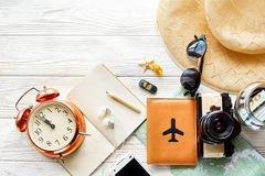 Time to travel concept, space for text. map camera passport mone. Y phone with empty screen sunglasses and clock hat shells car toy on white wooden background Stock Image