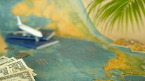 Time to travel concept. Tropical vacation theme with world map, blue passport and plane. Preparing for holliday, journey. Trip items with copy space. North stock video footage