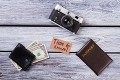 Time to travel essentials. Flat lay, top view. Photo camera, passport, and wallet with cash on wooden table Stock Image