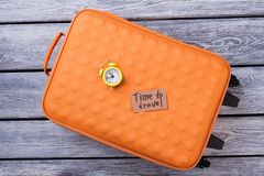 Time to travel flat lay. Orange suitcase and alarm clock Royalty Free Stock Image