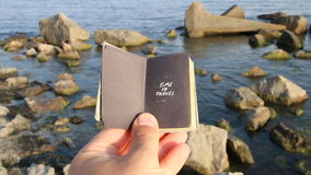 Time to travel idea, hand holding a book with the inscription and rocks on the sea. Time to travel, book with the inscription and beach stock video