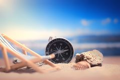 Time to Travel. Idea for tourism with compass and chaise lounge on the sand with corals on the background of the sea. Time to Travel. Idea for tourism with stock photography