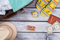Time to travel items arrangement flat lay. Top view. Travel necessities on wooden table surface Royalty Free Stock Photo