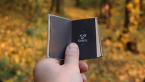 Time to travel. Vacation idea. Hand holding a book with the inscription Time to travel. Autumn wood on a background stock video