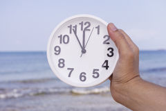 Time to travel. Woman holding clock against sea. Vacation concept stock images