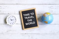 Time to travel the world. Top view of table clock,globe of world map and blackboard written with inspirational quotes & x27;TIME TO TRAVEL THE WORLD& x27; on Royalty Free Stock Photos