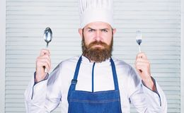 Time to try taste. Chef serious face hold spoon and fork. Man handsome with beard holds kitchenware on white background stock photo