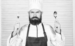Time to try taste. Chef serious face hold spoon and fork. Man handsome with beard holds kitchenware on white background stock image