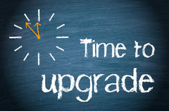 Time to upgrade concept. Drawing on a clock next to the words time to upgrade on a blackboard or chalkboard, business concept Stock Photos