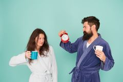 Time to wake up and have nice day. Guy husband hold coffee and clock. Every morning begins with coffee. Couple in. Bathrobes with mugs. Man with beard and royalty free stock images