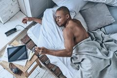 Time to wake up. Top view of young African man checking the time Stock Photo