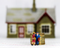 Time to Walk. A couple who have just been evicted from there house carrying suitcases, also a pile of gold coins placed in front signifying the debt they are Stock Image