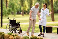 The doctor helps the patient to walk on crutches. Wheelchair left behind. Time to walk in the park. A young female doctor helps the patient to walk on crutches Royalty Free Stock Photo
